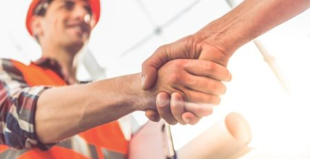 Construction worker in hard hat shaking hands with someone