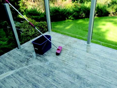 CLEANING VINYL DECKING - IMAGE OF BUCKET AND BRUSH ON DECK SURFACE - TUFDEK VINYL
