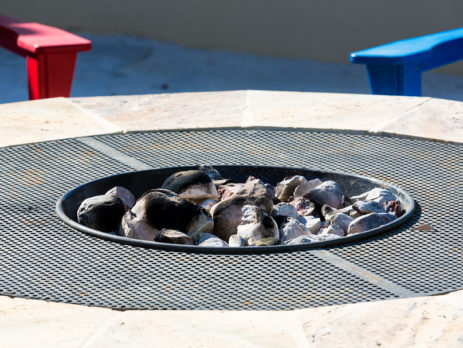 Concrete fire pit with a red bench and blue bench in the background