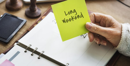 IMAGE OF WOMAN'S HAND HOLDING CARD THAT SAYS LONG WEEKEND - TUFDEK