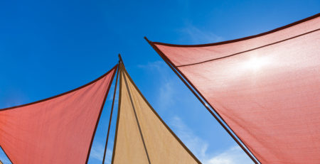 IMAGE OF COLOURFUL DECK SUN SHADES AGAINST A BLUE SKY - TUFDEK