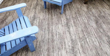 2 blue wooden lawn chairs on a newly covered vinyl wood plank deck