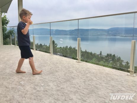Barefoot child blowing bubbles on newly installed balcony vinyl flooring