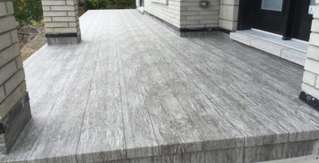 Finished vinyl wood plank decking on the front deck of a home