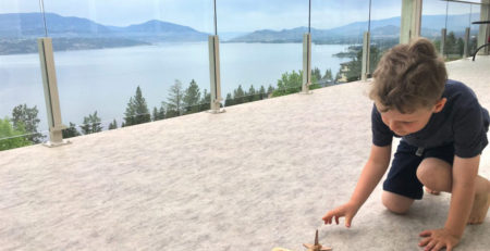 Child playing with toy on vinyl deck with view of lake in background
