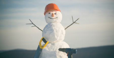 Snowman with construction hat, saw and electric drill