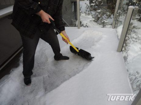 Man shovelling snow off a vinyl deck