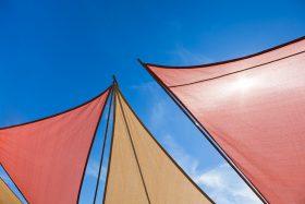 Image of colourful deck sun shades against a blue sky - Tufdek