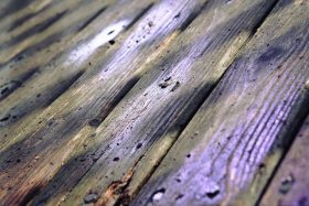 Image of damaged wooden deck surface - paint vs vinyl decking - Tufdek